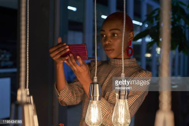 young woman with short haircut checking her makeup on her phone - red dress fotografías e imágenes de stock