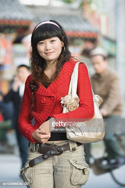 Young woman with shoulders bag on street, smiling, portrait
