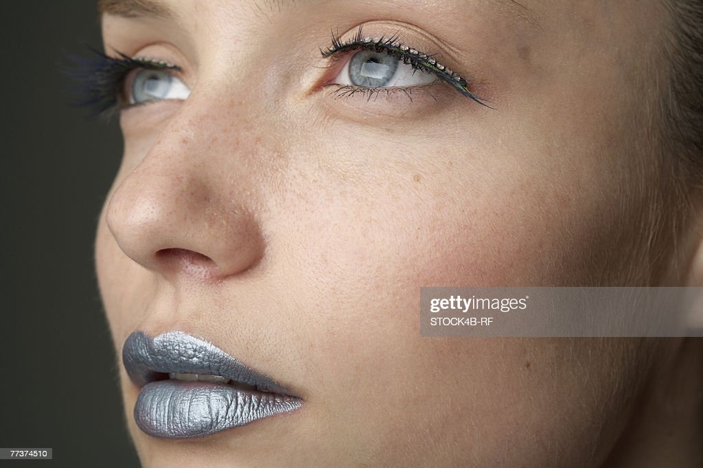Young woman with silver colored lips (part of), close-up : Stock Photo