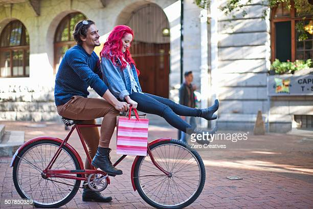 Young woman with sitting on boyfriends bicycle handlebars, Cape Town, South Africa