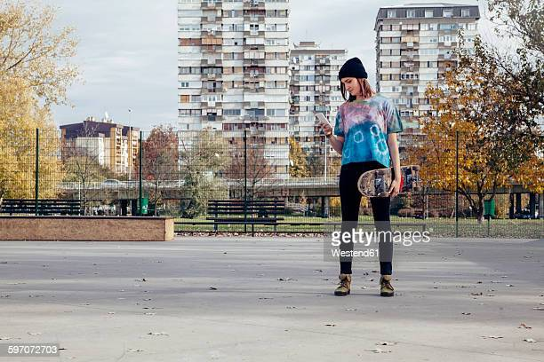 Young woman with skateboard looking at cell phone