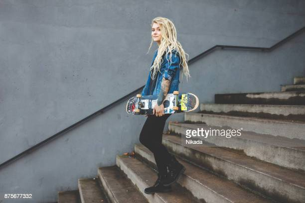 Young woman with skateboard on staircase