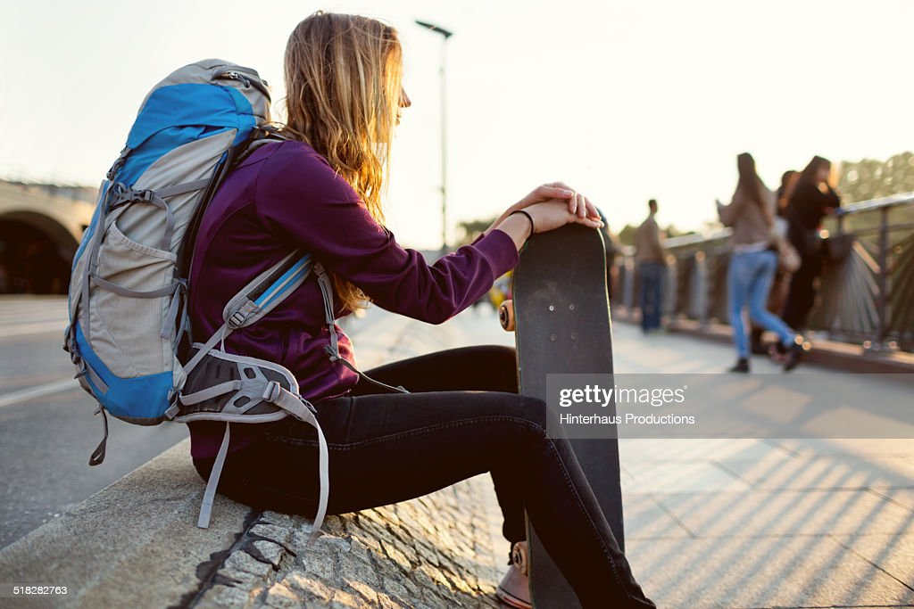 Young woman with skateboard and backpack sitting outdoor and watching sunset