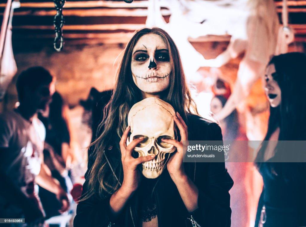 Jovem mulher com crânio de exploração maquiagem esqueleto na festa de Halloween : Foto de stock