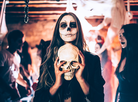 Young woman with skeleton make-up holding skull at Halloween party 916493964