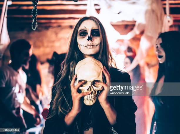 Young woman with skeleton make-up holding skull at Halloween party