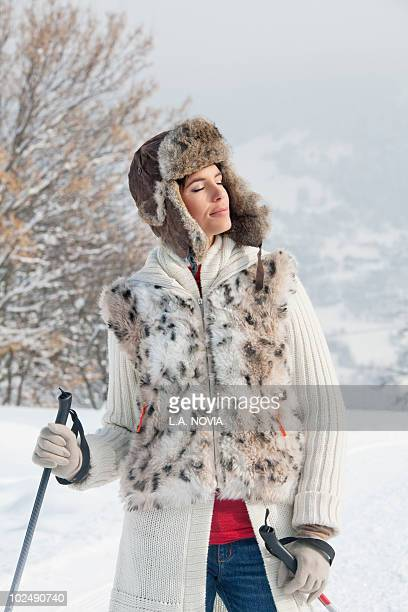 young woman with ski poles, eyes closed - fur hat stock photos and pictures
