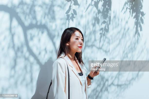 young woman with smart phone against the plain wall with sunlight - smart stock pictures, royalty-free photos & images