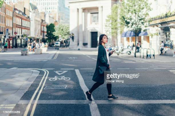 young woman with smart phone, crossing the road in the city - high street stock pictures, royalty-free photos & images
