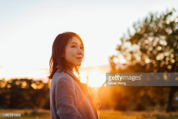 young woman with smart phone enjoying nature - social media stock pictures, royalty-free photos & images