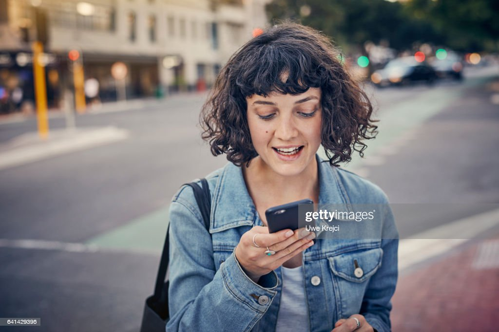 Young woman with smart phone in the city : Stock Photo