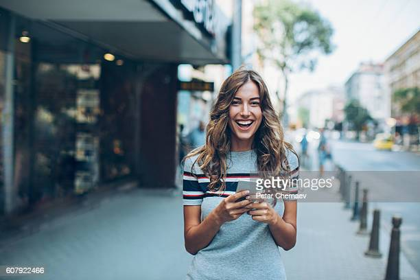 Young woman with smart phone laughing on the street