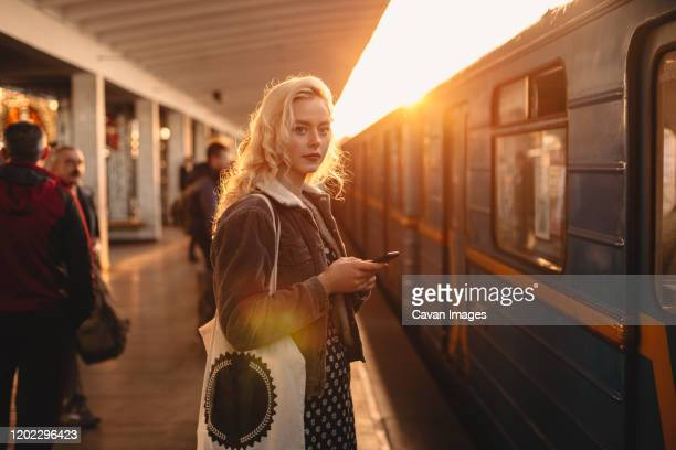 young woman with smart phone standing at subway station - golden hour stock pictures, royalty-free photos & images