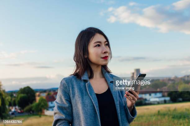 young woman with smart phone under blue sky - travel destinations stock pictures, royalty-free photos & images
