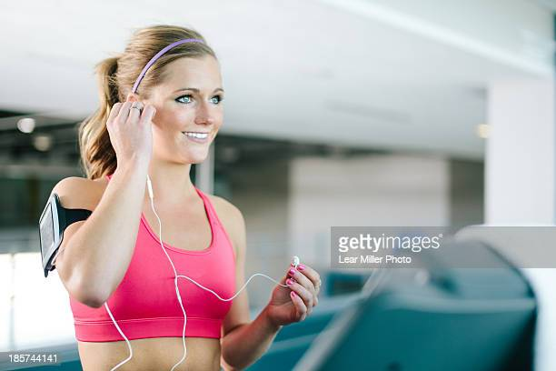 young woman with smartphone armband and earplugs - positioning stock pictures, royalty-free photos & images