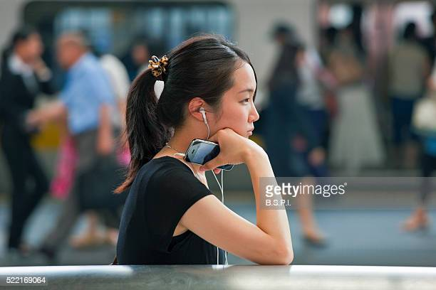 Young Woman with Smartphone at Shinjuku Station in Tokyo, Japan