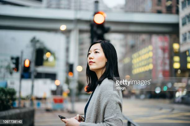 young woman with smartphone commuting in the city, against busy city traffic and highrise buildings - china oost azië stockfoto's en -beelden