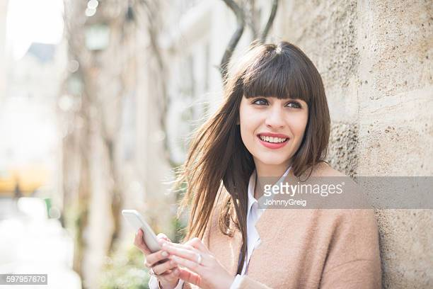 Young woman with smartphone looking away, smiling