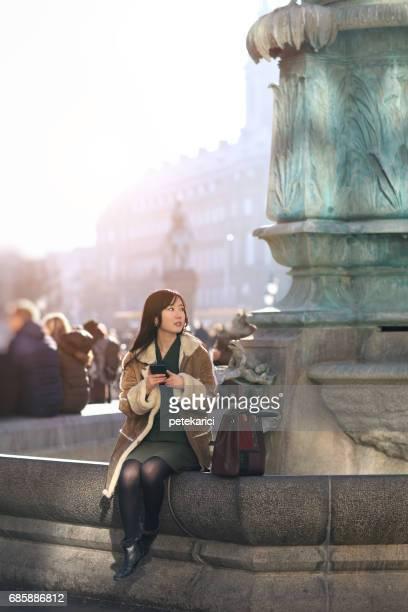 young woman with smartphone looking over her shoulder in city, Copenhagen