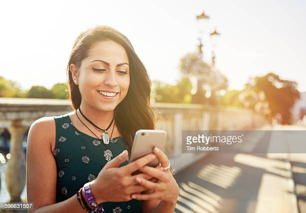 Young woman with smartphone on bridge.