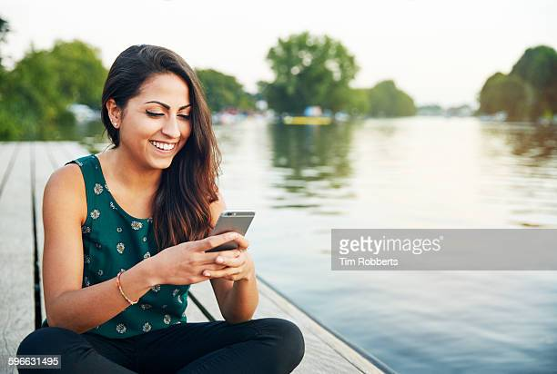 Young woman with smartphone on jetty.
