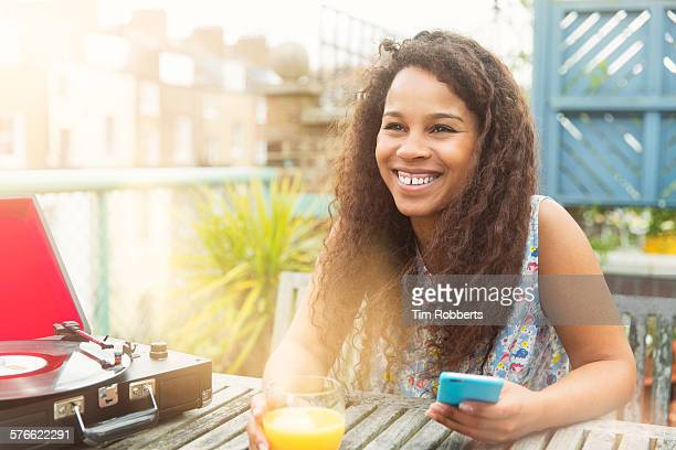 Young woman with smartphone on terrace.