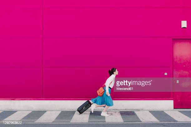 young woman with smartphone running with trolley along a pink wall - woman hurry stockfoto's en -beelden