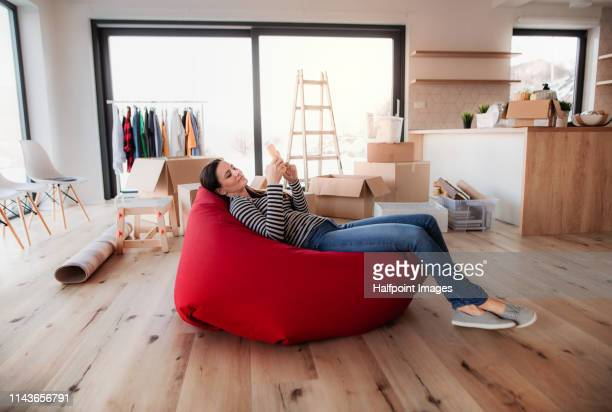young woman with smartphone sitting on bean bag among moving boxes in a new home. - sacco photos et images de collection