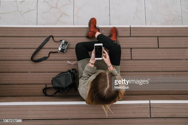 young woman with smartphone sitting on staircase - camera girls stock photos and pictures