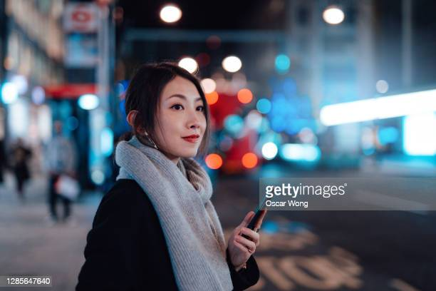 young woman with smartphone waiting for taxi in the city at night - equipment stock pictures, royalty-free photos & images