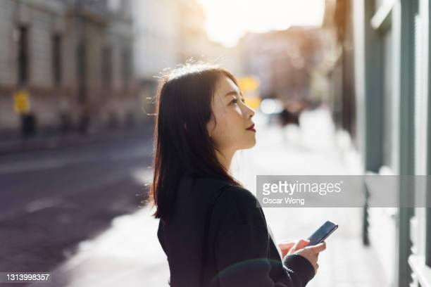 young woman with smartphone walking on the street in the city - reflection stock pictures, royalty-free photos & images