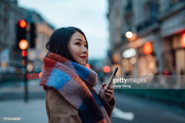 young woman with smartphone walking on urban city street - business finance and industry stock pictures, royalty-free photos & images
