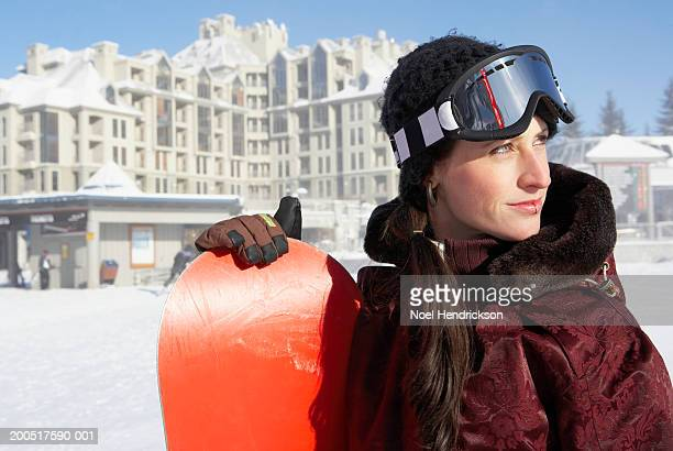 Young woman with snowboard wearing ski goggles, looking away