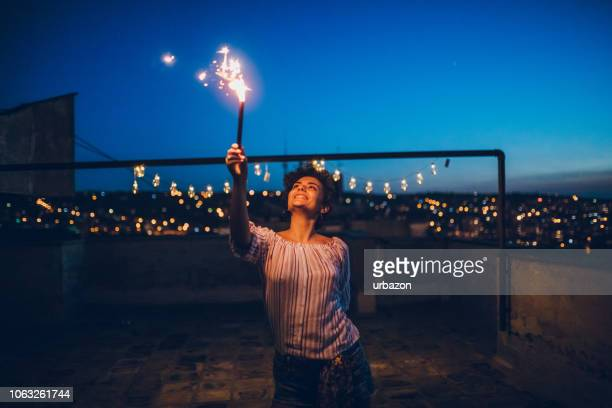 young woman with sparkler on rooftop - terraced field stock pictures, royalty-free photos & images