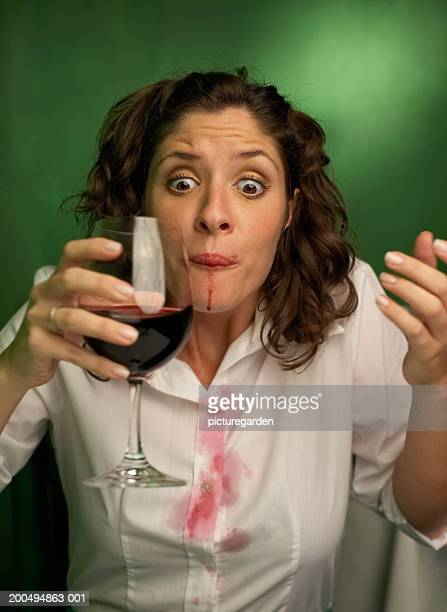 Young woman with spilt red wine on mouth and shirt