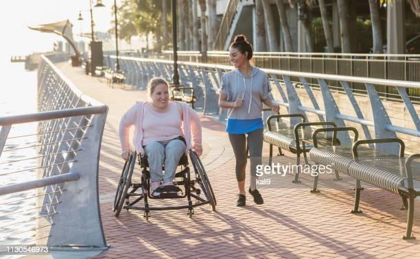Young woman with spina bifida, Hispanic friend jogging