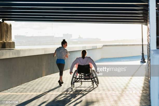 young woman with spina bifida, hispanic friend jogging - wheelchair stock pictures, royalty-free photos & images