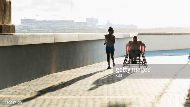 Jeune femme avec le spina bifida, le jogging d'ami hispanique