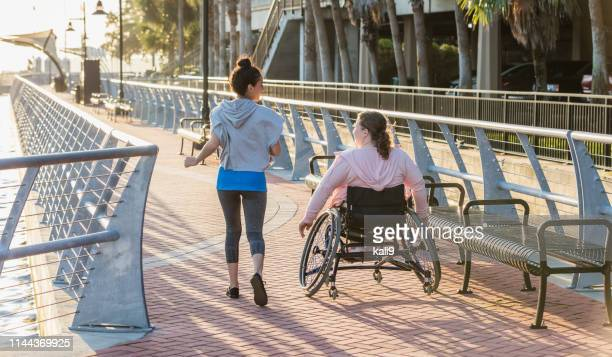 young woman with spina bifida, hispanic friend jogging - of deformed people stock pictures, royalty-free photos & images
