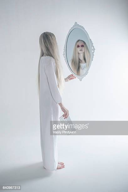 Young woman with spooky red eyes looking in mirror against white background