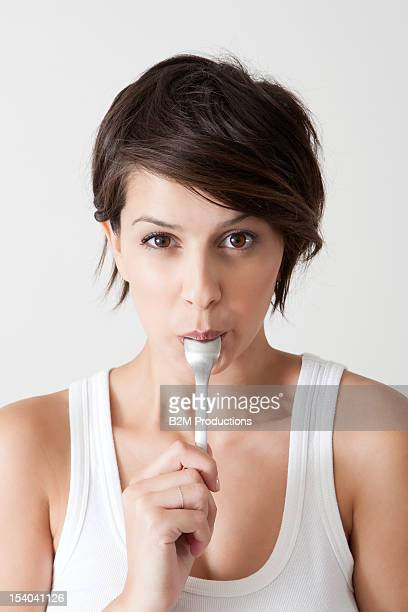 Young Woman With Spoon In Mouth