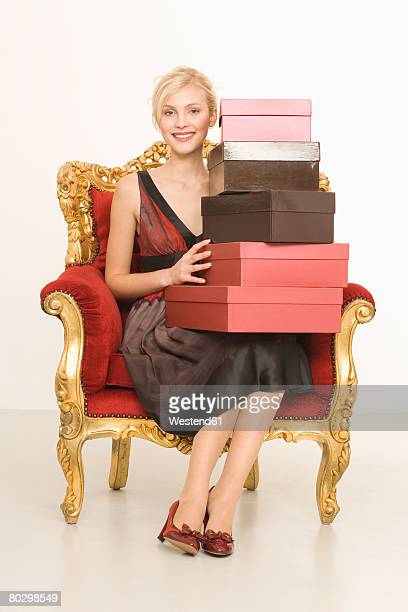 Young woman sitting on throne with stack of shoe boxes, smiling, portrait