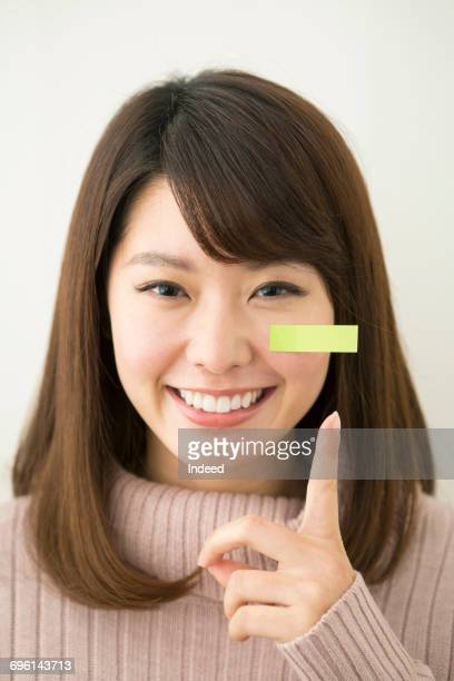 Young woman with sticky note smiling