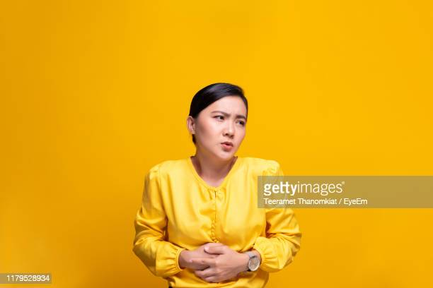 young woman with stomachache against yellow background - 下痢 ストックフォトと画像