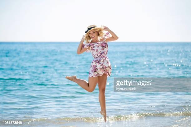 ビーチでジャンプ麦わら帽子を持つ若い女性 - サンドレス ストックフォトと画像