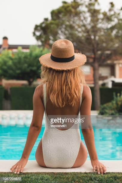young woman with straw hat sitting at poolside, rear view - chica morena de espaldas fotografías e imágenes de stock
