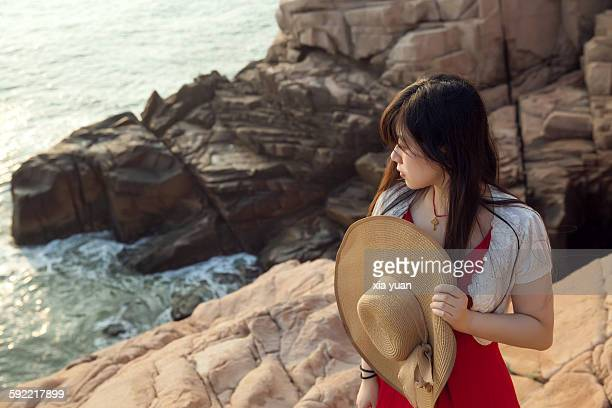 Young woman with straw hat standing on cliff edge