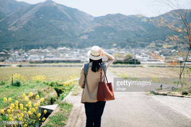 young woman with straw hat walking outdoors in the nature on a oilseed rape field - 旅 ストックフォトと画像