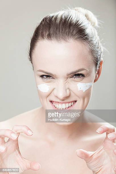 young woman with streaks of lotion on face - cheek stock pictures, royalty-free photos & images