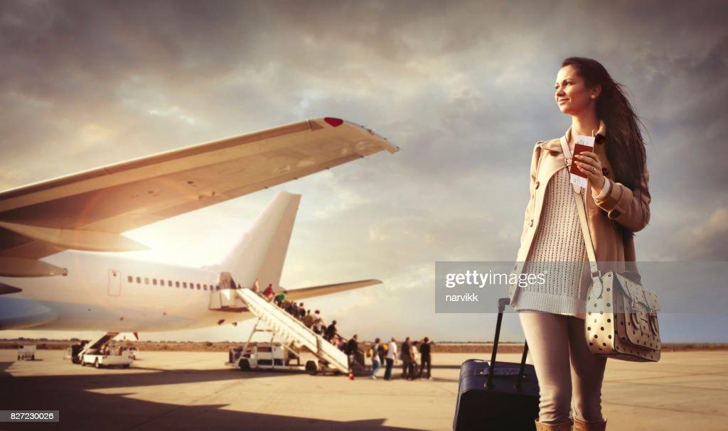 Junge Frau mit Koffer am Flughafen angekommen : Stock-Foto